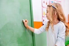 Mädchen-Schreiben auf grüner Tafel im Kindergarten stockbild