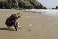 Mädchen-Schreiben im Sand auf dem Strand Stockbilder