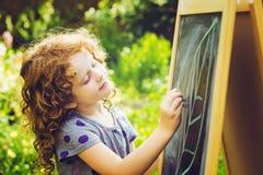 Mädchen schreibt in Kreide auf eine Tafel getrennte alte Bücher tonen Stockbilder