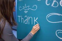 Mädchen schreibt Kreideglückwunsch auf das blaue Brett stockfotografie
