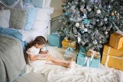 Mädchen schreibt Santa Claus einen Brief im Raum mit Bett und im Weihnachtsbaum in den Blau- und Goldfarben lizenzfreie stockbilder
