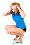Mädchen schreit, während sie ihr Gewicht auf der Skala sieht Lizenzfreie Stockbilder