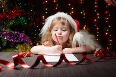 Mädchen schrieb Santa Claus im roten Bleistift einen Brief Stockbilder