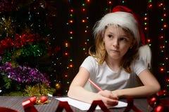 Mädchen schrieb Santa Claus im roten Bleistift einen Brief Lizenzfreies Stockbild