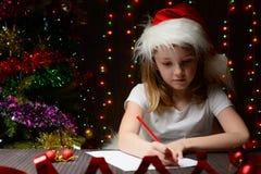 Mädchen schrieb Santa Claus im roten Bleistift einen Brief Stockfoto