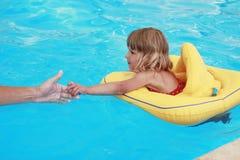 Mädchen schwimmt in einem Pool mit einem Kreis Stockfotografie