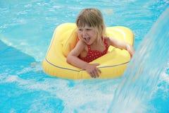 Mädchen schwimmt in einem Pool mit einem Kreis Stockbild