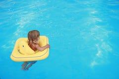 Mädchen schwimmt in einem Pool mit einem Kreis Lizenzfreie Stockfotos