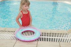 Mädchen schwimmt in einem Pool mit einem Kreis Stockfoto