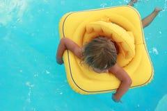 Mädchen schwimmt in einem Pool mit einem Kreis Stockfotos