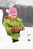 Mädchen sculpt vom Schnee viel Schneemann Stockfotografie