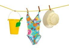Mädchen setzen Abnutzung und Spielwaren auf Kleidungzeile auf den Strand Stockbild