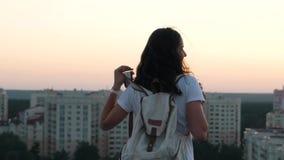 Mädchen setzt einen Rucksack auf das Dach stock footage