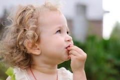 Mädchen setzt sich in ihre Mundbeere stockbild