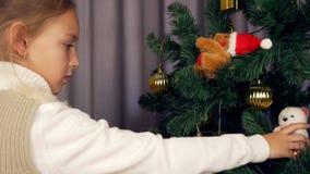 Mädchen setzte das Spielzeug auf den Tannenbaum Weihnachtsabend, weißes kaukasisches Mädchen, das einen Weihnachtsbaum verziert S stock video