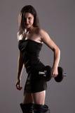 Mädchen in sexy schwarzes Kleideranhebenden Gewichten Stockbild