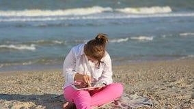 Mädchen siebzehnjährig mit Down-Syndrom auf dem Strandspiel mit der Tablette stock footage
