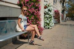 Mädchen Siiting auf einer Bank Stockbilder