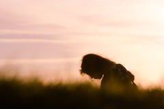 Mädchen silhouettiert im Profil vor purpurrotem Sonnenuntergang Lizenzfreie Stockfotografie