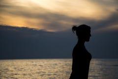 Mädchen silhuette am Strand während des Sonnenuntergangs lizenzfreies stockbild