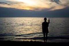 Mädchen silhuette am Strand während des Sonnenuntergangs lizenzfreies stockfoto