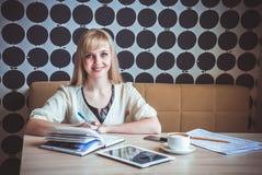 Mädchen simsende sms unter Verwendung des Handys im Café Lizenzfreie Stockbilder