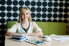 Mädchen simsende sms unter Verwendung des Handys im Café Stockfotografie