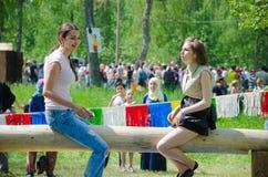 Mädchen sitzen auf einem Klotz und bereiten sich für Kampf auf Taschen vor lizenzfreies stockbild