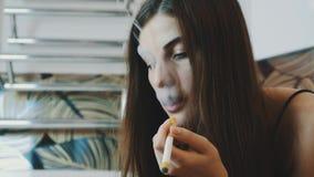 Mädchen sitzen in Badezimmerhahn Smartphone Rauchende elektronische Zigarette Atmen Sie Dampf aus stock video