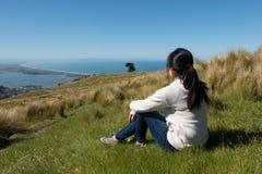 Mädchen sitzt auf Bergkuppe und betrachtet Stadt unten Stockfotografie