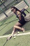 Mädchen sitzt auf dem Gras auf dem Tennisplatz Stockbild