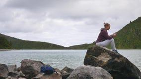 Mädchen sitzt auf dem Hintergrund von einem Gebirgssee mit einem Smartphone und benutzt Apps für Reisende stock video