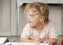 Mädchen sitzt auf einem Boden und einem Zeichnen Stockfotografie
