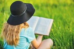 Mädchen sitzt auf einem Gras und liest ein Buch Stockfotos