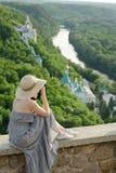Mädchen sitzt auf einem Hügel und macht Fotos eines Waldes und des Tempels Stockbild
