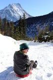 Mädchen sitzt auf einem Schlitten Stockfotos
