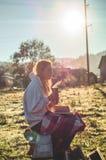 Mädchen sitzt auf einer Holzbank in den Bergen in der Natur, liest ein Buch, trinkt heißen Tee von einer Thermo Schale Konzepte,  lizenzfreies stockbild