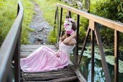 Mädchen sitzt auf einer kleinen Brücke in einem Blumenkranz Stockfotos