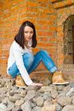 Mädchen sitzt an der alten Backsteinmauer Lizenzfreies Stockfoto