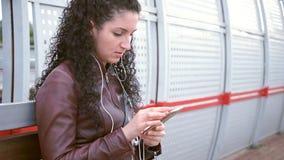 Mädchen sitzt an der Station und schreibt sms stock video footage