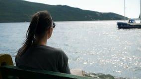 Mädchen sitzt durch das Meer auf einer Bank stock video
