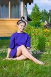 Mädchen sitzt im Gras im Sommergarten lizenzfreie stockfotos