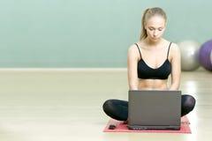 Mädchen sitzt mit dem Laptop in der Sportgymnastik Stockfotos