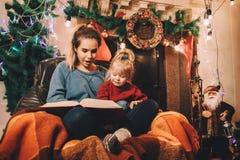 Mädchen sitzt mit ihrer kleinen Schwester und liest einen Märchenabend Stockbild