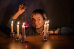 Mädchen sitzt nahe der Tabelle mit Kerzen in einer Dunkelkammer Lizenzfreies Stockfoto