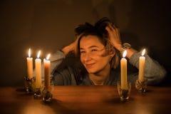 Mädchen sitzt nahe der Tabelle mit Kerzen in einer Dunkelkammer Lizenzfreie Stockfotos