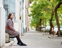 Mädchen sitzt nahe Wand im Profil auf Herbststraße Budapest Stockfotos