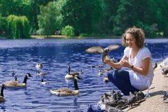 Mädchen speist Vögel stockbild