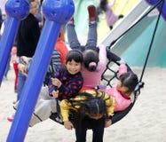 Mädchen spielen glücklich auf großem Nettoschwingen, luftgetrockneter Ziegelstein rgb Stockbilder
