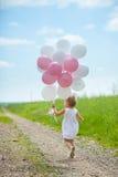 Mädchen spielt im Sommerpark mit bunten baloons Stockfotos